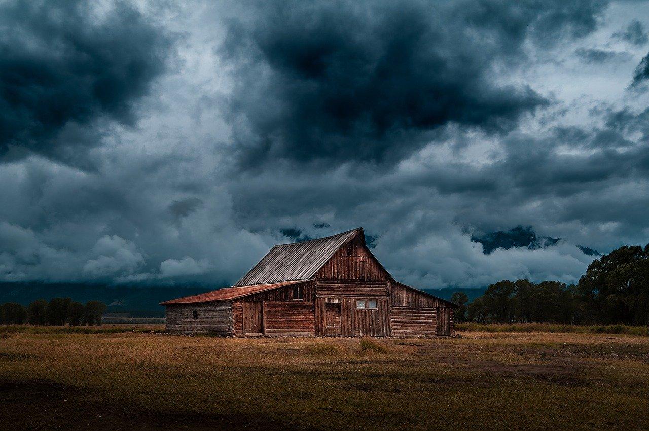 Une petite maison dans une plaine, avec en fond un ciel orageux