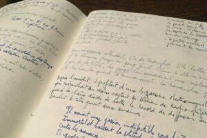 Un cahier dont les pages sont remplies d'histoires courtes et de microfictions manuscrites